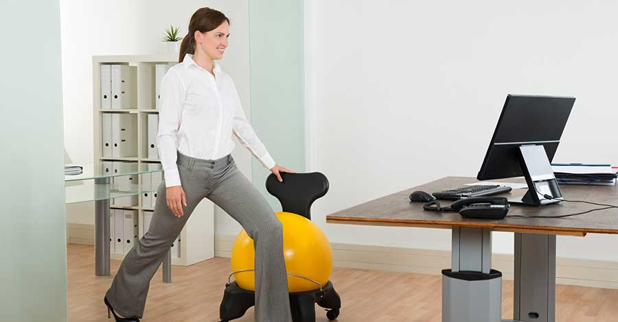 Bild zeigt Frau im Büro, die abwechselnd im stehen und sitzen arbeitet