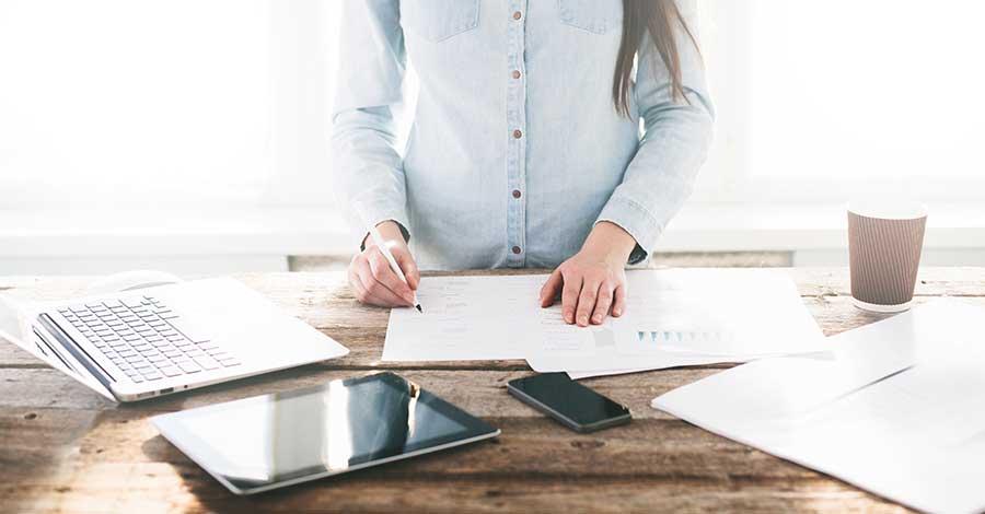 Bild von Frau an höhenverstellbaren Schreibtisch beim Arbeiten